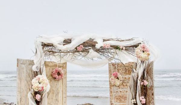 beach wedding ceremony with doors as backdrop