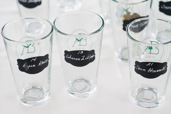Guests were greeted with escort glasses instead of cards;  the glasses had chalkboard paint with their name and table number already written on it.  Brilliant idea! | Photo: Searching for the Light Photography LLC | via http://emmalinebride.com/real-weddings/colorado-chic-wedding-kendall-brian/