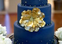 deep blue wedding cake with big gold flower