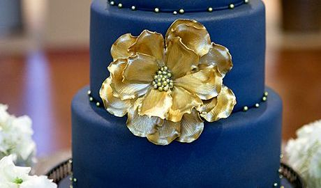 deep blue wedding cake with big gold flower