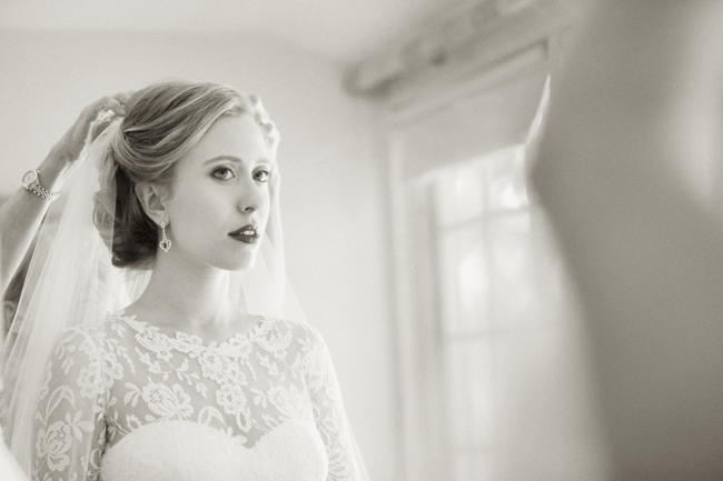 bride getting ready while looking in mirror at Connecticut waterfront wedding - photo: Melani Lust Photography | via http://emmalinebride.com