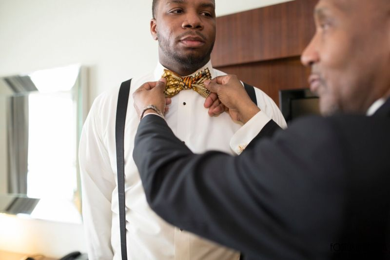 mansion on main street wedding - the groom putting on his bowtie