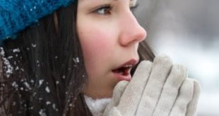Beautiful brunette girl outdoors in cold snow winter day