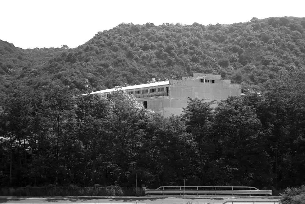 "A view from the LRF of the former industrial coater building (""Big Boy""), now empty and partially demolished and idling behind the lush trees in the valley carved by the Fiume Bormida - FILM FERRANIA P30, June 2017"