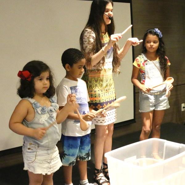 Em cima de um palco, Marília usa microfone head set. Está entre três crianças. Todas seguram colheres de pau.