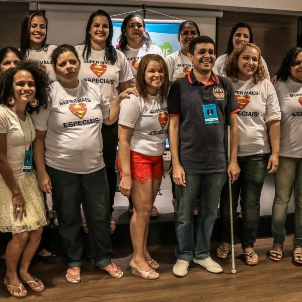 """Em frente a um pequeno palco 11 mulheres estão de pé, de frente para nós e usam blusas brancas onde lemos """"Super mães Especiais"""". Da esquerda para a direita, entre as mães, estão Priscila, Leonard e Bruna. Sorriem."""