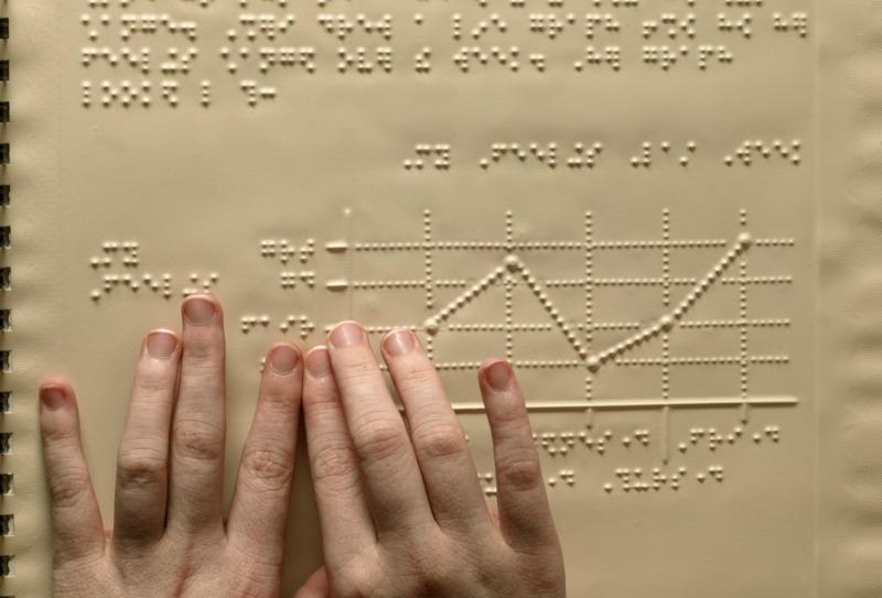 Duas mãos sobre uma folha com a escrita braille. Nela há textos e um gráfico.