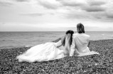 romantic bride and groom sitting on the beach in black and white