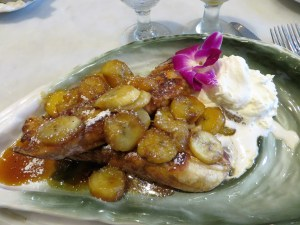 Bananas Foster Pain Perdu, garnished with an orchid.