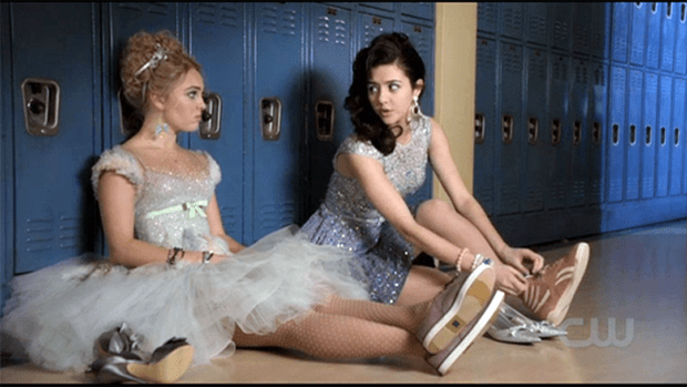 The Carrie Diaries' Annasophia Robb (as #TEENCARRIEBRADSHAW in lilac Keds and a winter Ballet dress by Georges Chakra ) and Katie Findlay (as Maggie Landers, Carrie's #toughgirl BFF, in rose Reeboks and a sleeveless Ice Skater dress by Asos) leave the boys behind and change out of their dancing shoes. Carrie's peep toe heels are silver satin with a silver crystal center bow, Maggie's are silver glittered kitten heels by Nina.