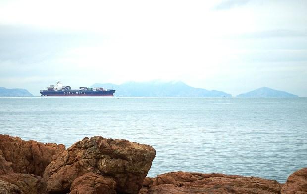 Et skip fra Yang Ming seiler gjennom Lamma-kanalen på vei inn mot den gedigne havna i Hong Kong.