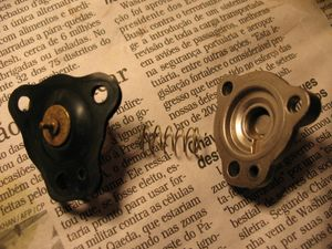 O diafragma suplementar, sua mola e sua tampa, demonstrando a ordem correta de montagem. O sistema suplementar serve para enriquecer a mistura em altos regimes do motor. Como o sistema principal do carburador não consegue fornecer essa proporção, o sistema suplementar entra em ação. Só assim o motor pode desenvolver sua potência máxima. O vácuo aciona o diafragma suplementar, que por sua vez aciona a válvula de máxima, que permite a adição de combustível à mistura.
