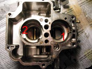 """O corpo do carburador, já totalmente """"pelado"""". Por ser um serviço um pouco mais complexo, e que requer relativamente rara manutenção, não vamos remover os eixos das borboletas. Caso apresentem folgas (folgas nos eixos geram entradas falsas de ar), é aconselhável mandar refazer os embuchamentos em loja especializada. Os estrangulamentos nos corpos do carburador são chamados de difusores primários (venturis). Na foto, venturi do primeiro estágio (1) e venturi do segundo estágio (2). Eles estreitam a passagem do ar, acelerando-o, e criando um vácuo que causa a succção do combustível. Em alguns carburadores, é possível retirar e substituir os venturis por outros de diâmetro diferente. No caso do Weber 460, os venturis são fixos no corpo do carburador, e só podem ser alargados através de usinagem."""