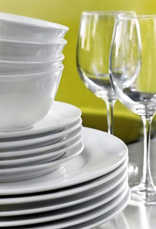 Stack of Commercial White Plates Bowls and Wine Glasses