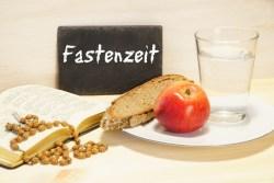 Fastenzeit, Tafel mit Schrift, Gebetbuch, Brot, Apfel, Glas Wasser