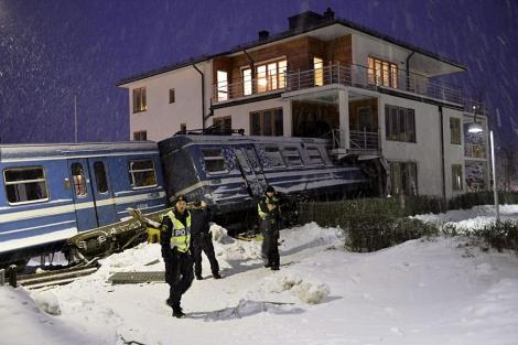 Policías suecos junto al tren empotrado en un bloque de viviendas.   Reuters