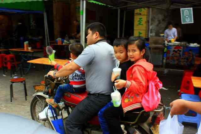 A Chinese family on a bike holding their breakfast