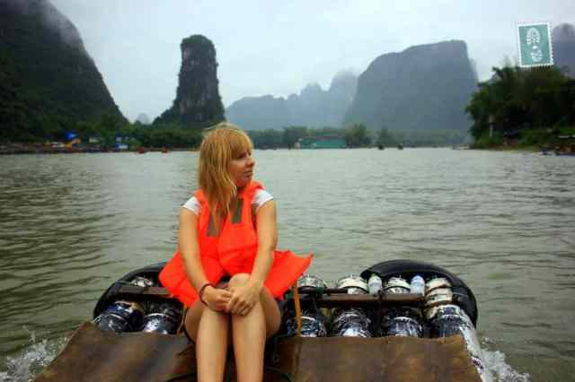 A girl sitting on a bamboo boat Yangshuo River