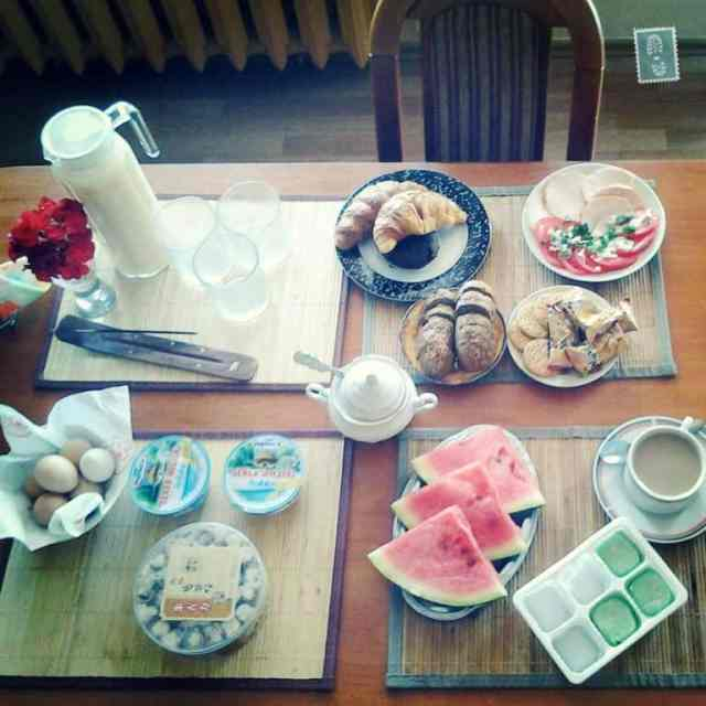 Breakfast table with croissants, milk, ham, cookies, fruits