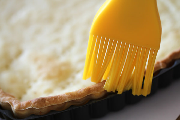 Brush the tart shell with egg wash.