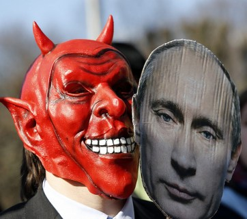 An activist wears a devil's mask which he covers with a picture of Vladimir Putin as part of a protest against the Russian President outside the congress center of the Hanover trade fair on April 7, 2013 in Hanover, western Germany. Putin arrived for the official opening of the industrial trade fair with German Chancellor Angela Merkel (not in pic). Activists and critics said Putin should be held to account for a recent crackdown on non-governmental organisations promoting democratic reforms in Russia. Image: AFP PHOTO / ODD ANDERSEN