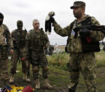 Russian mercenaries taking photographs with personal items found among the debris at the crash site of MH17 downed by a Russian BUK surface-to-air missile in Russia-occupied east Ukraine (Image: Dmitry Lovetsky/AP)