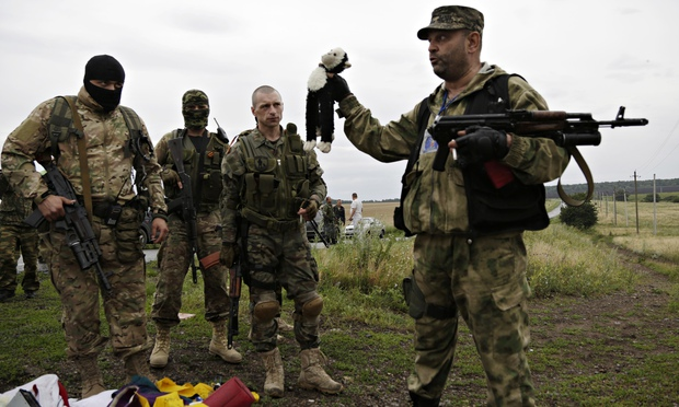 Representatives of Putin's 'Russian world' taking photographs with personal items they found among the debris at the crash site of Malaysia Airlines flight MH17 with 298 people aboard downed by a Russian BUK surface-to-air missile in Russia-occupied east Ukraine (Image: Dmitry Lovetsky/AP)