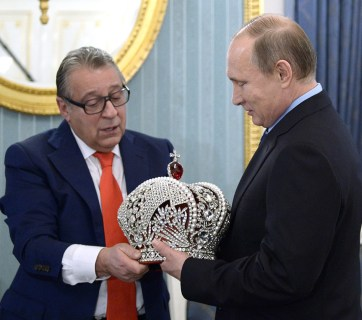 Gennady Khazanov, an acclaimed Russian comedic actor loyal to the Putin regime, presenting the Russian president with a reproduction of the Russian imperial crown made for Putin's 63rd birthday. (Image: meduza.io)
