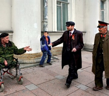 A street scene in St. Petersburg, Russia, the city where Vladimir Lenin's group launched the Bolshevik coupe d'etat of 1917. Lenin and Stalin impersonators giving money to a beggar maimed in one of Putin's wars. (Image: Alexander Petrosyan)