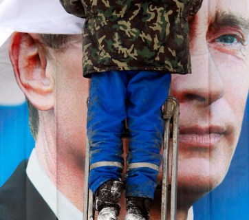 Putin poster being hung (Image- vedomosti.ru)