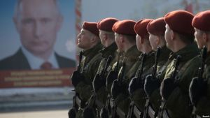 Soldiers of the National Guard of Russia, an internal security structure directly subordinated to Putin, in front of his portrait
