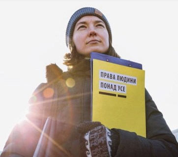 "Woman holds leaflet with the words ""Human rights above all."" Photo by Reyana Bakshyshova"