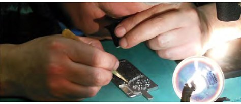 A watchmaking specialist positions turned hard metal parts to prepare them to receive the stone.