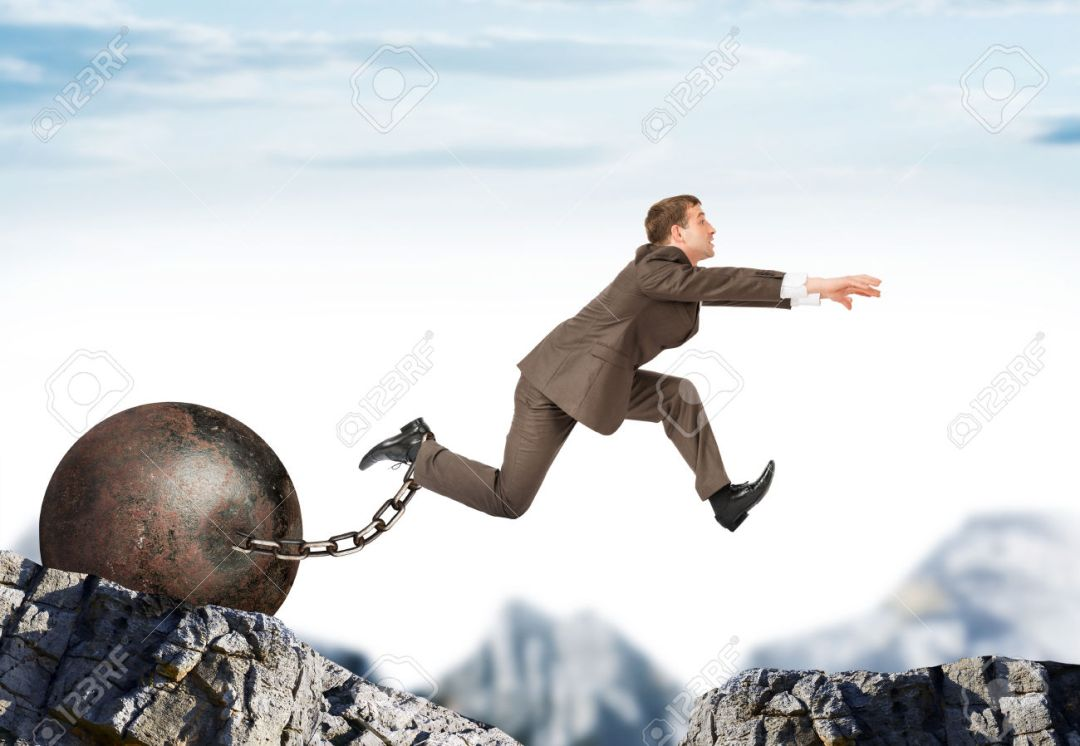 Businessman with iron ballast  hopping over bottomless pit
