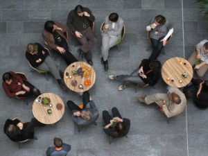 A group of people sit around tables, drinking coffee