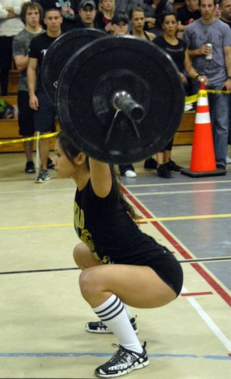 Girl performing the overhead squat exercise