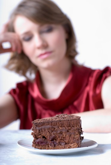 Woman thinking about eating a piece of cake
