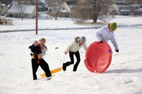 Teens and children sledding in the snow