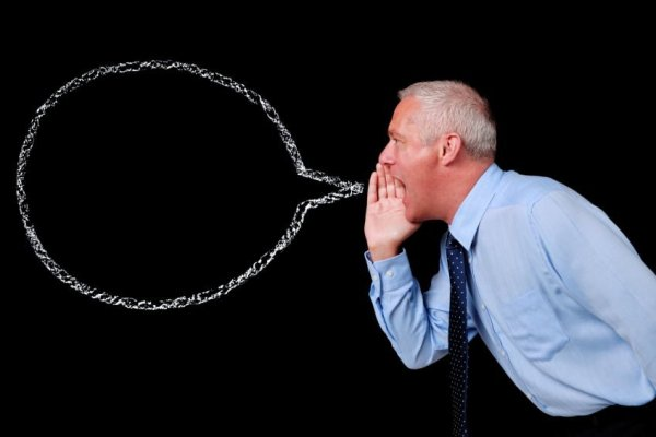 Photo of a mature businessman shouting against a black background, chalk speech bubble with copy space to add your own text.