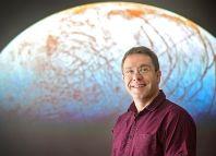 """El Dr Jonti Horner delante de una imagen del satélite de Júpiter, Europa. """"Es otro lugar en nuestro sistema solar, donde podría haber vida"""", dijo."""