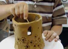 Kinderhände formen ein Tongefäß