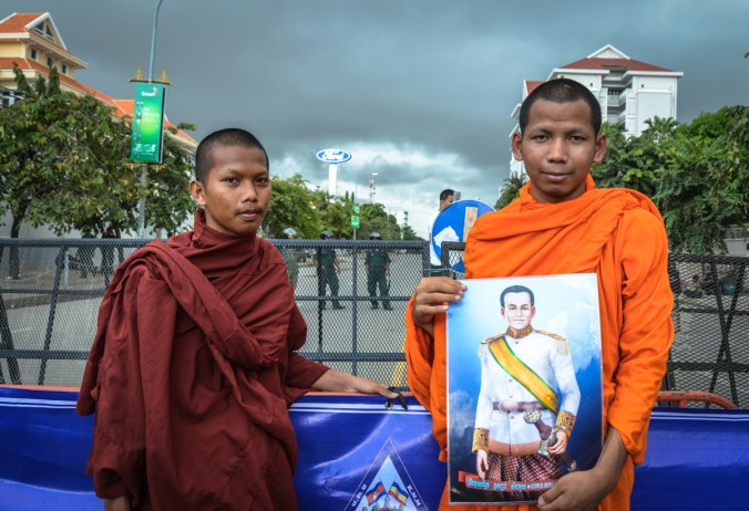Monks pose with an image of Kampuchea Krom hero Son Kuy.