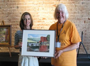 Tommie Fester of Steelville Drugs is shown presenting Joyce Hartmann with one of two purchase awards at the Steelville MO plein air competition. This watercolor was done on location at Dillard Mill.