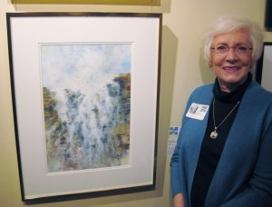 """Diana Foote stands next to her award-winning watercolor """"Seaside Waterfall"""" at the Mid-Southern Watercolorists Exhibition in Little Rock. (photo by Mike Foote)"""
