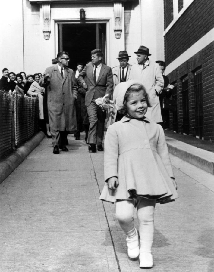 Caroline Kennedy walks ahead while her father, the most powerful man in the world, carries her doll. (1960).