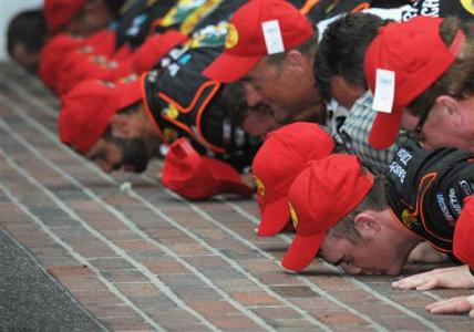 Ty Dillon, driver of the #3 Bass Pro Shops Chevrolet, and his team celebrate by kissing the bricks after winning the NASCAR Nationwide Series Lilly Diabetes 250 at Indianapolis Motor Speedway on July 26, 2014 Photo - Rainier Ehrhardt/Getty Images