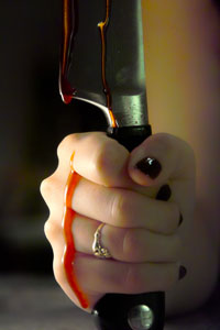 A hand holding a bloody knife.