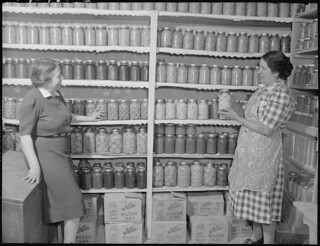 New Mexico. Mrs. Fidel Romero Proudly Exhibits Her Canned Food. [Two Women Standing in a Kitchen Pantry. Pantry Contains Preserved Fruits and Vegatables.] 1946