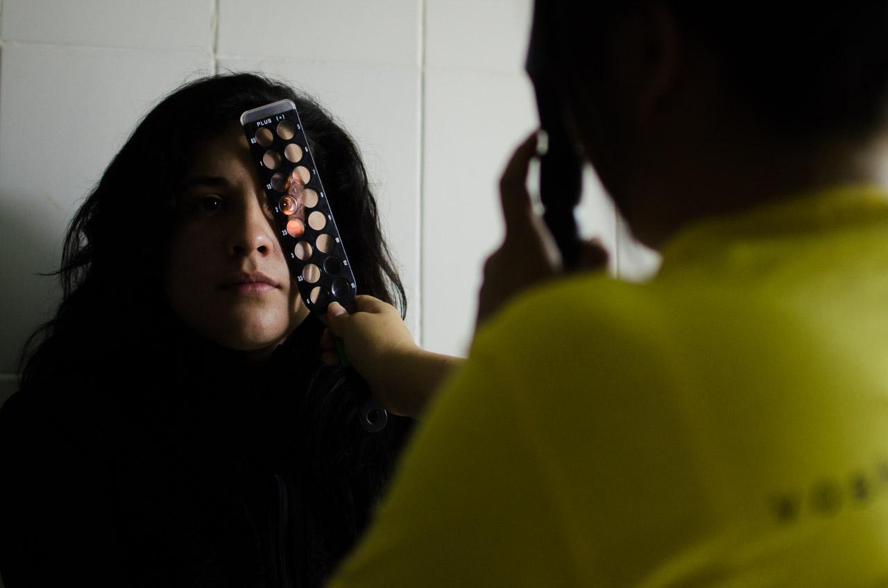 La voluntaria Gloria Young realiza un exámen de refracción a una paciente a través de un método convencional debido a la falta de energía eléctrica que impedía el uso de instrumentos automáticos. El resultado de este examen determina la presencia de un error en la vista del paciente y la sucesiva prescripción de anteojos para corregirlo. (Elton Núñez)