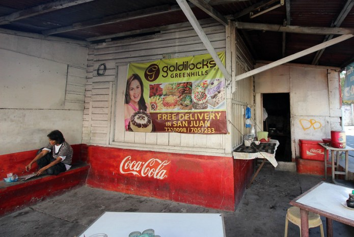 coca cola painted on store with a woman on a bench